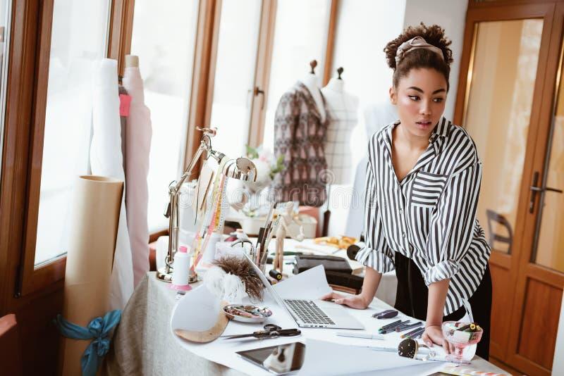 Junger Modedesigner am Arbeitsplatz, afrikanische Frau, die zu jemand schaut stockbild