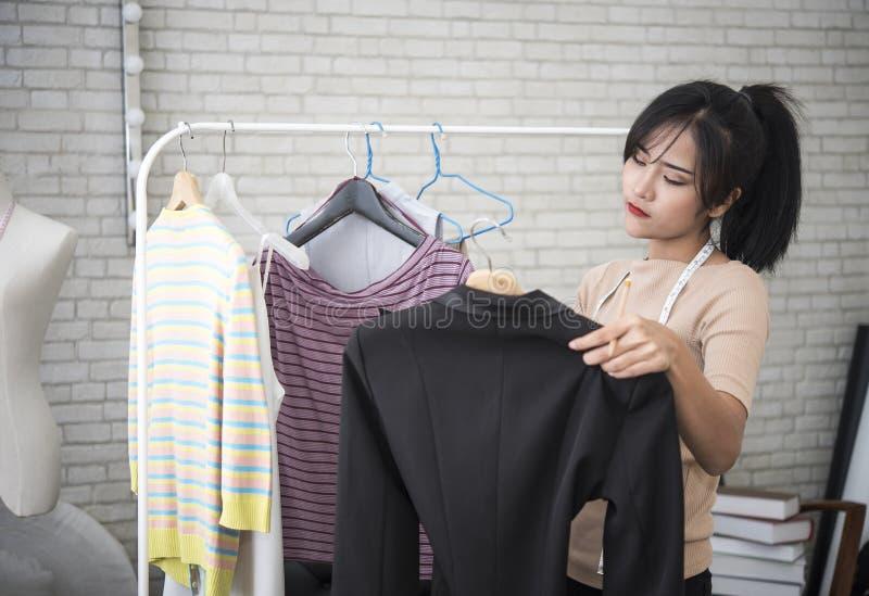 Junger Modedesigner, der für Näherinkleid im Studio arbeitet lizenzfreie stockfotos