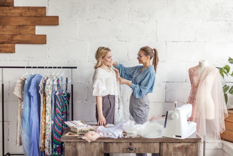 Junger Modedesigner, der Maße einer Frau nimmt, um neues Kleid zu entwerfen stockfotos