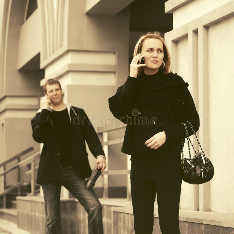 Junger Modemann und -frau mit Handtasche um Handy ersuchend lizenzfreies stockbild