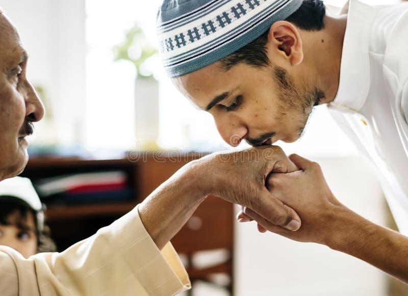 Junger moslemischer Mannvertretungsrespekt zu seinem Vater stockbilder