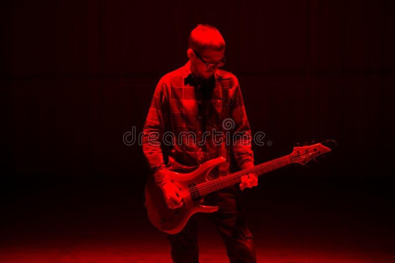 Junger Musiker, der die eklektische Gitarre im roten Licht spielt stockfotografie