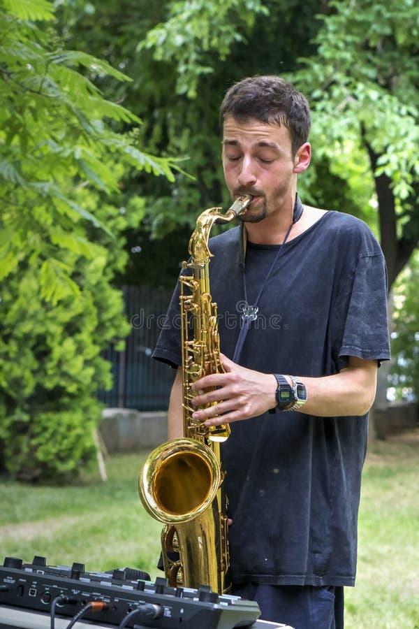 Junger Musiker, der Straßenmusik auf Saxophon durchführt stockfotos