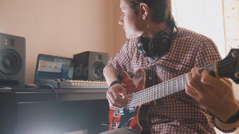 Junger Musiker verfasst und notiert die Filmmusik, welche die Gitarre unter Verwendung des Computers, der Kopfhörer und der Tasta lizenzfreie stockfotografie