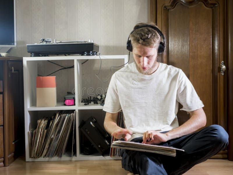 Junger Musikfreundmann, in zufälligem und in den Kopfhörern mit Vinylaufzeichnungen zu Hause in sitzen stockbilder