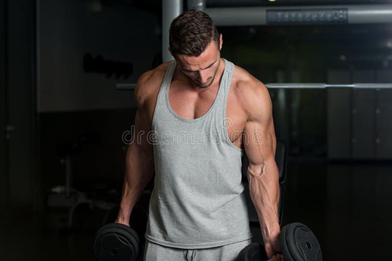 Junger muskulöser Mann-anhebende Gewichte stockfotos