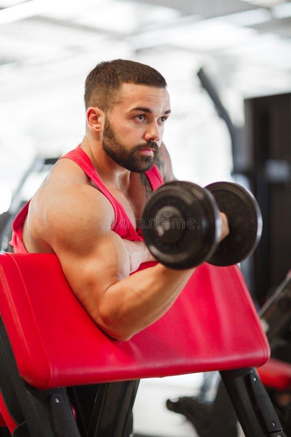 Junger muskulöser Mann, der Sport in der Turnhalle tut Getrennt auf Weiß lizenzfreie stockfotografie