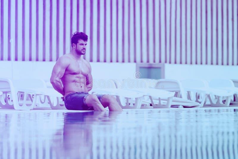 Junger muskul?ser Mann am Schwimmen Pools des im Freien stockfotografie