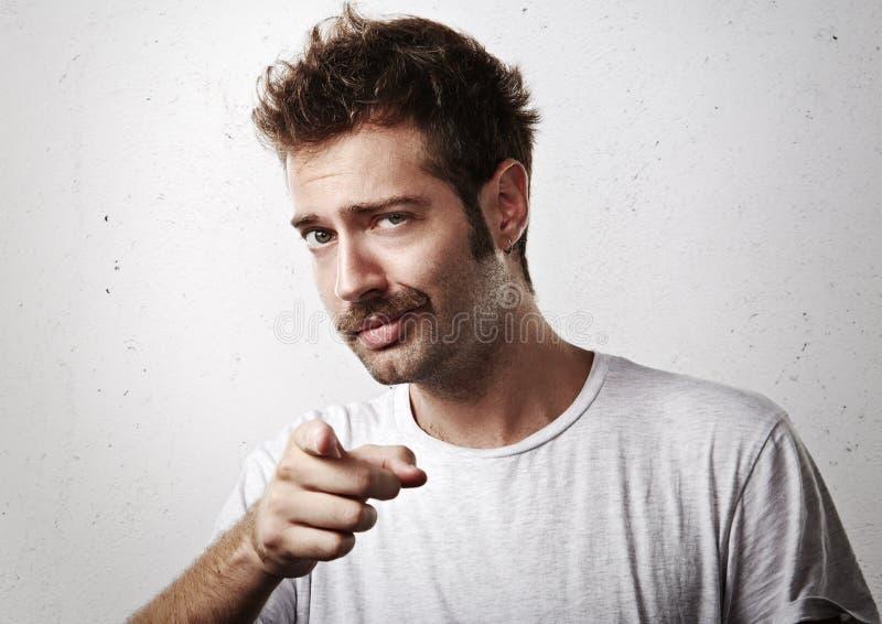Junger mustached Mann, der in Richtung zur Kamera zeigt lizenzfreies stockfoto