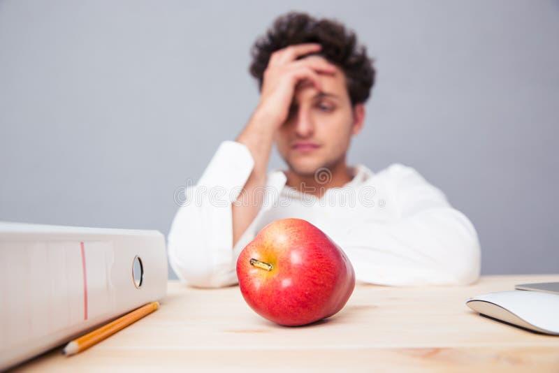 Junger nachdenklicher Geschäftsmann, der am Tisch sitzt stockfoto
