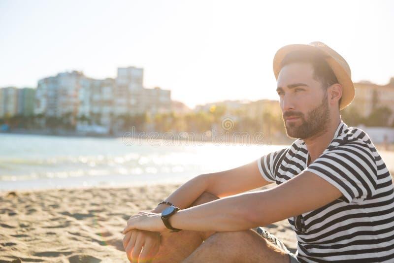 Junger nachdenklicher Mann im Hut, der auf dem Strand weg schaut sitzt stockbilder
