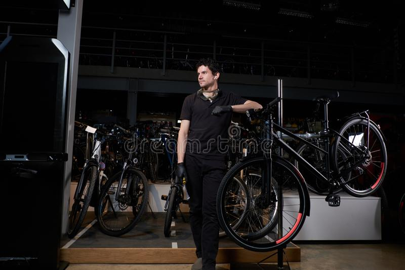 Junger nachdenklicher Meister kühlt nahe bei Fahrrad nach langem hartem Tag an seiner Werkstatt stockfoto