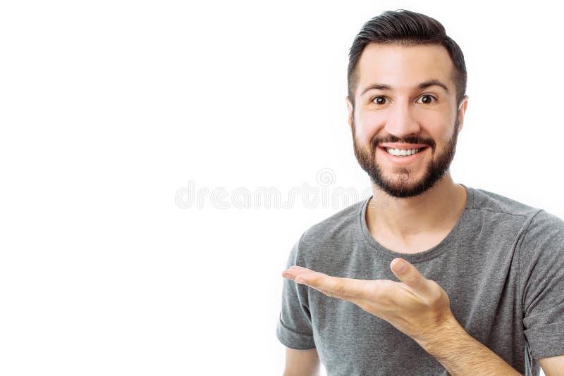 Junger netter bärtiger Mann, der Finger auf leeren Raum auf BAC zeigt lizenzfreie stockfotografie