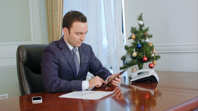 Junger netter Geschäftsmann unter Verwendung der modernen digitalen Tablette im Büro stockfotografie