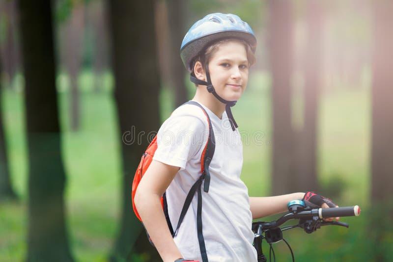 Junger netter Junge im Sturzhelm fährt Fahrrad im Park Junge geht auf die Straße Sport, stockfotografie