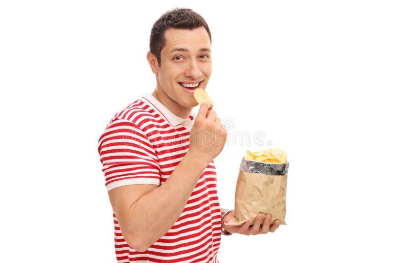 Junger netter Kerl, der Kartoffelchips isst lizenzfreie stockfotos