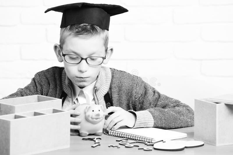 Junger netter Schülerjunge in der grauen Strickjacke und die Gläser, die am Schreibtisch mit hölzernen Zahlen des Schreibhefts si lizenzfreie stockbilder