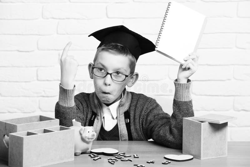 Junger netter Schülerjunge in der grauen Strickjacke und die Gläser, die am Schreibtisch mit hölzernen Zahlen des Schreibhefts in lizenzfreies stockbild