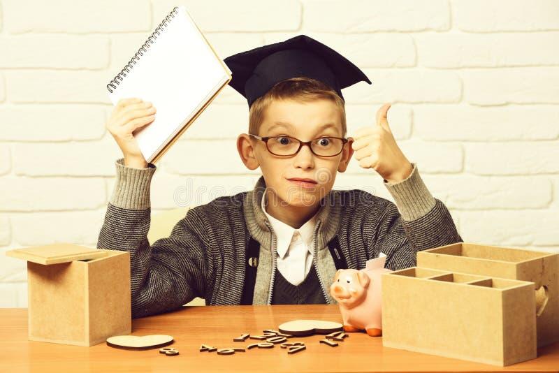 Junger netter Schülerjunge in der grauen Strickjacke und die Gläser, die am Schreibtisch mit hölzernen Zahlen des Schreibhefts in stockbilder