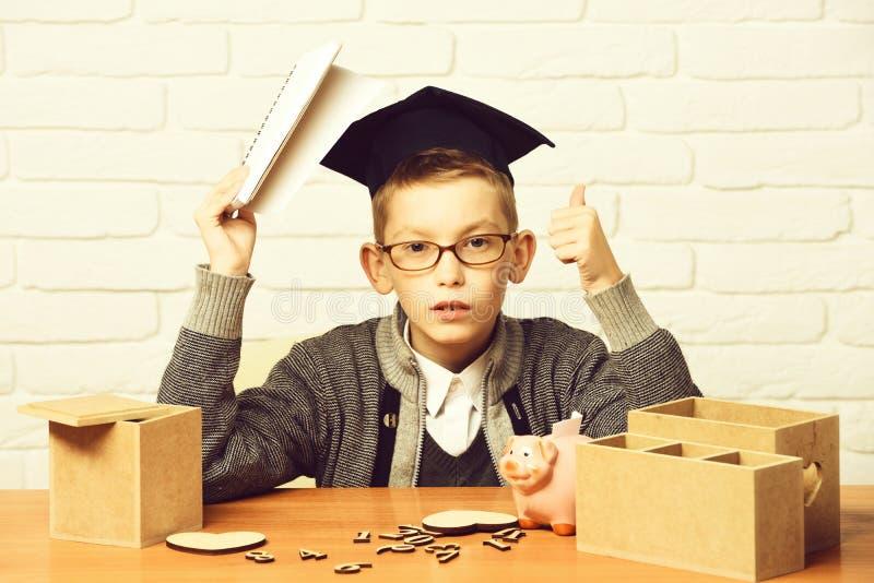 Junger netter Schülerjunge in der grauen Strickjacke und die Gläser, die am Schreibtisch mit hölzernen Zahlen des Schreibhefts in lizenzfreie stockfotografie