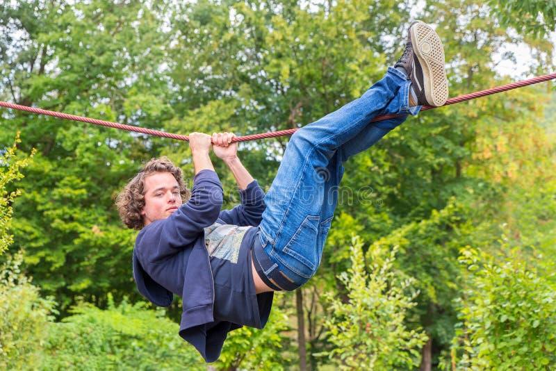 Junger niederländischer Mann, der draußen entlang Seil klettert stockfoto