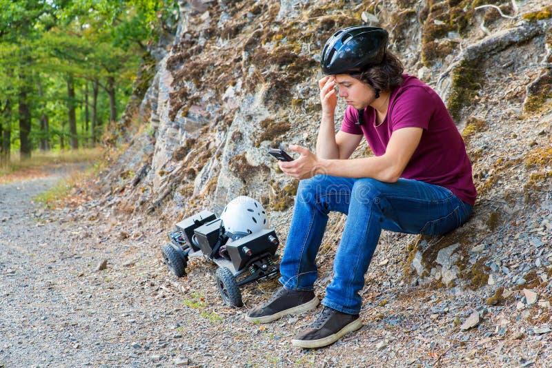 Junger niederländischer Mann sitzt mit mountainboard und Mobiltelefon lizenzfreie stockfotos