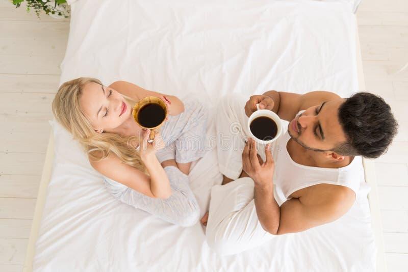 Junger Paar-Getränk-Kaffee, der im Bett, im glückliches Lächeln-hispanischen Mann und Frauen-in der Spitzenwinkelsicht sitzt lizenzfreies stockbild