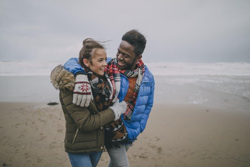 Junger Paar-Weg entlang Winter-Strand stockbilder