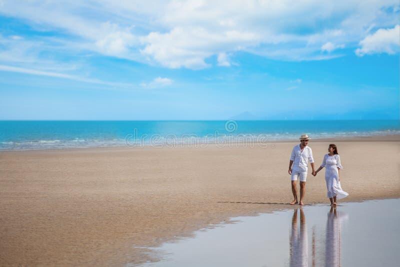 Junger Paarasiat in der Liebe Hand am Seestrand auf blauem Himmel gehend und zusammenhalten glückliche lächelnde Hochzeit mit wei lizenzfreie stockfotos