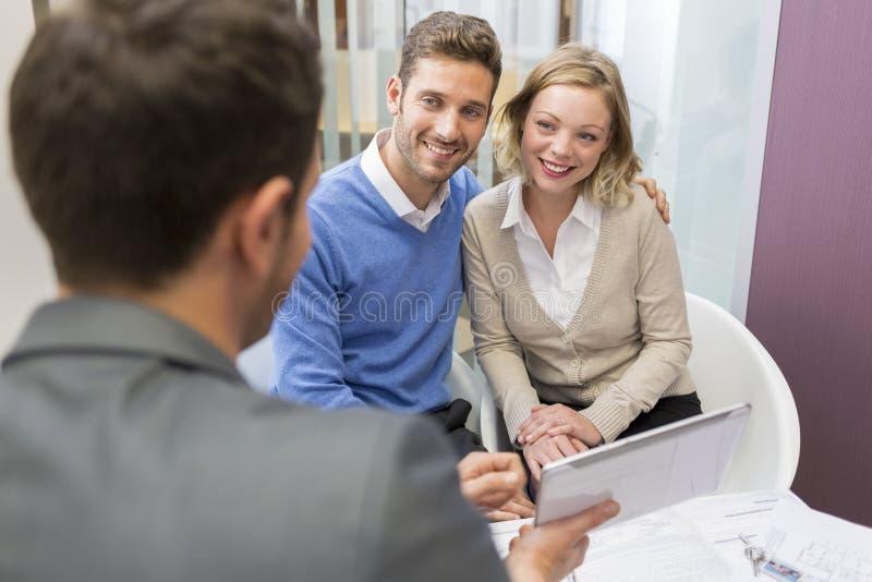 Junger Paarsitzungswirklichzustand, der an ein Investitionsvorhaben zeigt lizenzfreie stockbilder