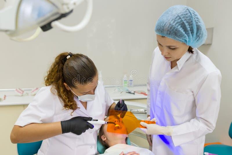 Junger Patient im zahnmedizinischen Stuhl Medizin-, Zahnheilkunde-und Gesundheitswesen-Konzept lizenzfreie stockfotos