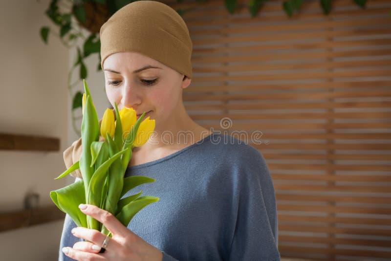Junger positiver Krebspatient der erwachsenen Frau, der Blumenstrauß von gelben Tulpen und von Lächeln hält Kämpfen mit Krebs stockfotos