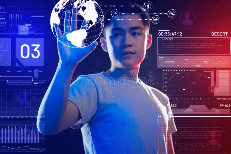 Junger Programmierer, der ein realistisches Erdhologramm hält und es betrachtet stockfoto