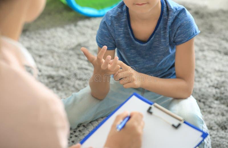 Junger Psychologe, der mit kleinem Jungen arbeitet stockbild