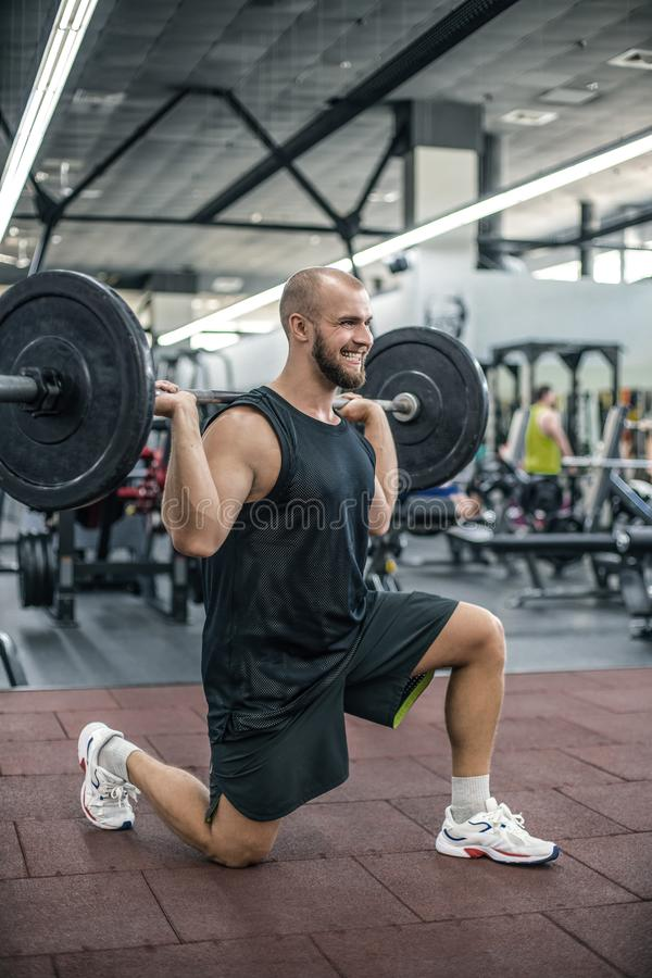 Junger querer geeigneter Athlet, der Hocken mit Barbell tut Mann, der Funktionstraining ?bt Powerlifting-Trainings?bungen stockfoto
