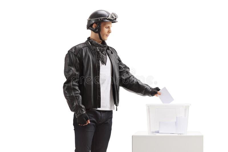 Junger Radfahrer, der eine Abstimmung in eine Wahlurne abgibt stockbild