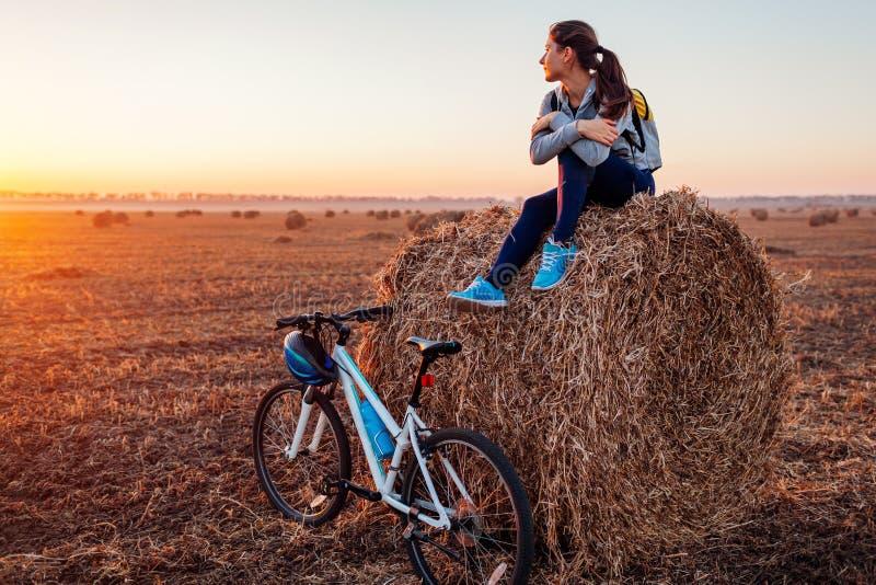 Junger Radfahrer, der Rest nach einer Fahrt auf dem Herbstgebiet bei Sonnenuntergang hat Frau, welche die Ansicht sitzt auf Heusc stockfoto