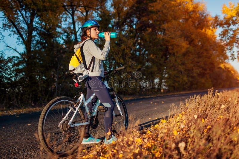 Junger Radfahrer, der Rest nach einer Fahrt auf dem Herbstgebiet bei Sonnenuntergang hat Trinkwasser der Frau auf Straße stockbilder