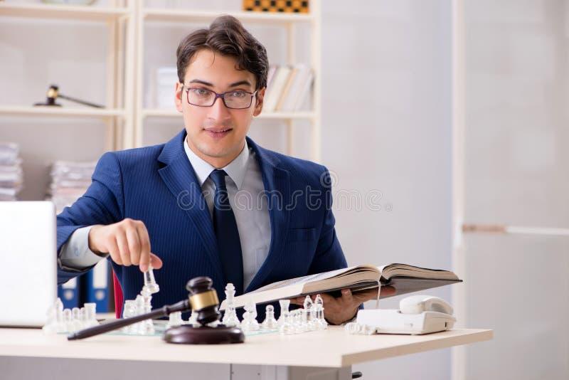 Junger Rechtsanwalt, der Schach spielt, um seine Gericht Strategie und tacti auszubilden lizenzfreie stockfotografie