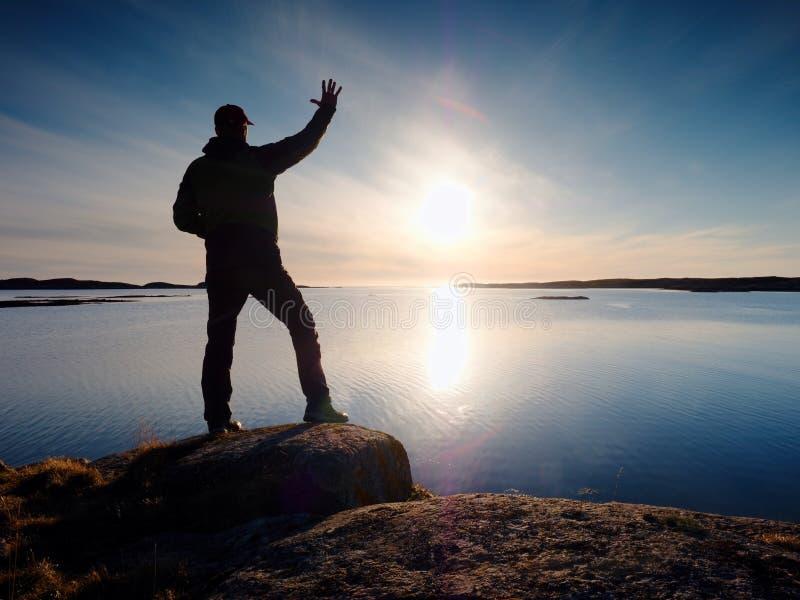 Junger Reisender, der auf Stein steht und an der Sonne aufpasst lizenzfreie stockfotos