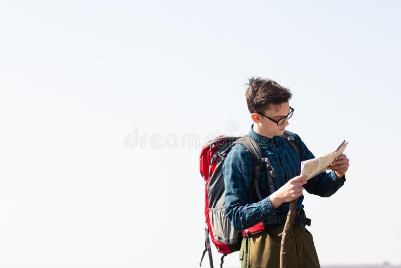 Junger Reisender mit dem Rucksack, der die Karte nach Richtungen beim Wandern in der Landschaft betrachtet stockfotografie
