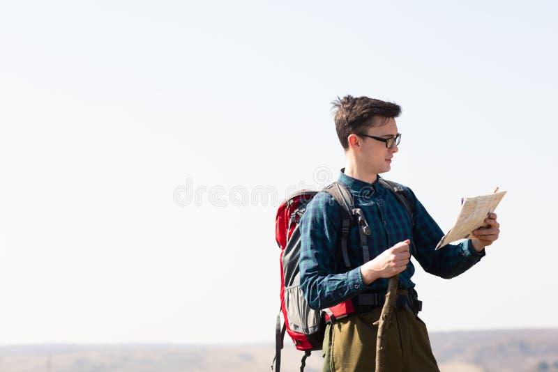Junger Reisender mit dem Rucksack, der die Karte nach Richtungen beim Wandern in der Landschaft betrachtet lizenzfreie stockfotografie