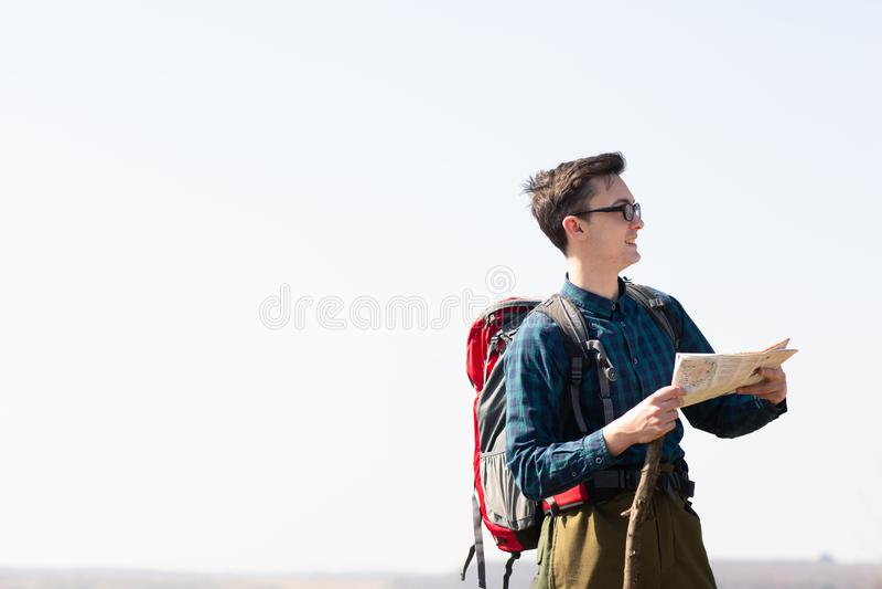 Junger Reisender mit dem Rucksack, der die Karte nach Richtungen beim Wandern in der Landschaft betrachtet stockfoto