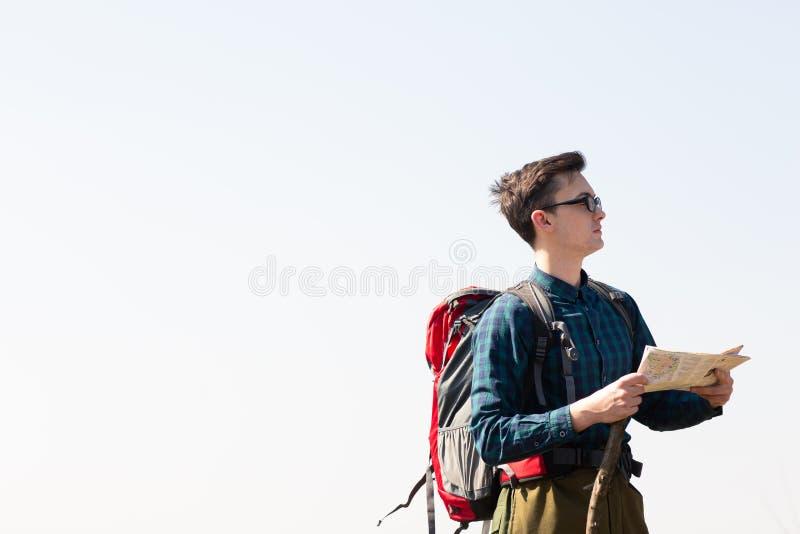 Junger Reisender mit dem Rucksack, der die Karte nach Richtungen beim Wandern in der Landschaft betrachtet lizenzfreie stockbilder