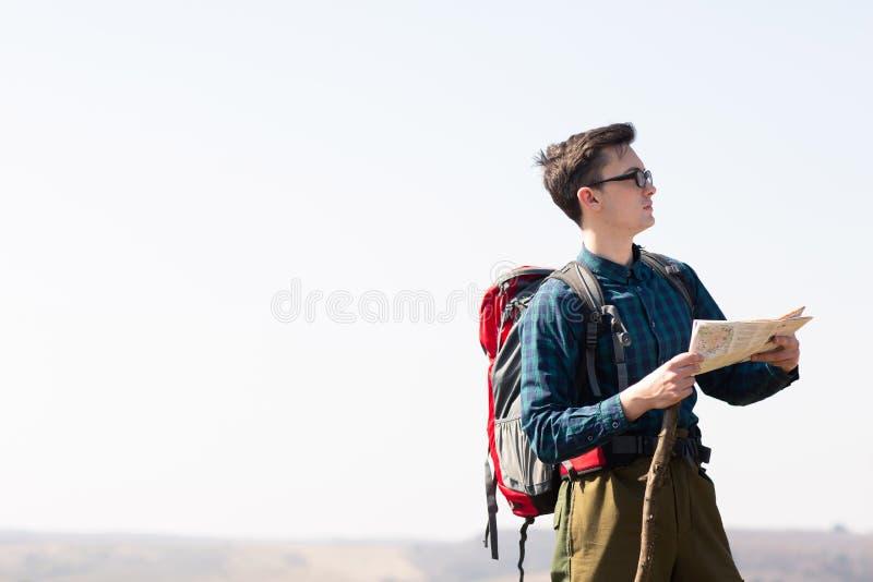 Junger Reisender mit dem Rucksack, der die Karte nach Richtungen beim Wandern in der Landschaft betrachtet lizenzfreies stockbild