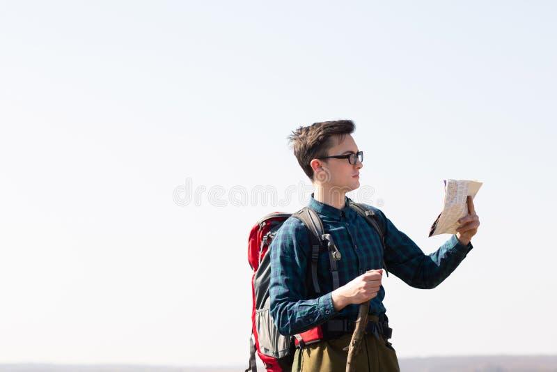 Junger Reisender mit dem Rucksack, der die Karte nach Richtungen beim Wandern in der Landschaft betrachtet lizenzfreie stockfotos