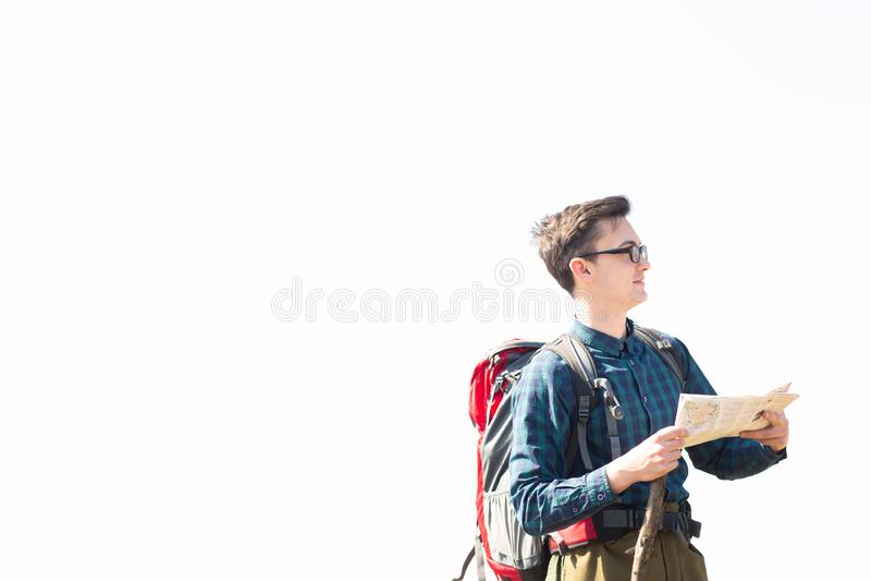 Junger Reisender mit dem Rucksack, der die Karte nach Richtungen beim Wandern in der Landschaft betrachtet stockbilder