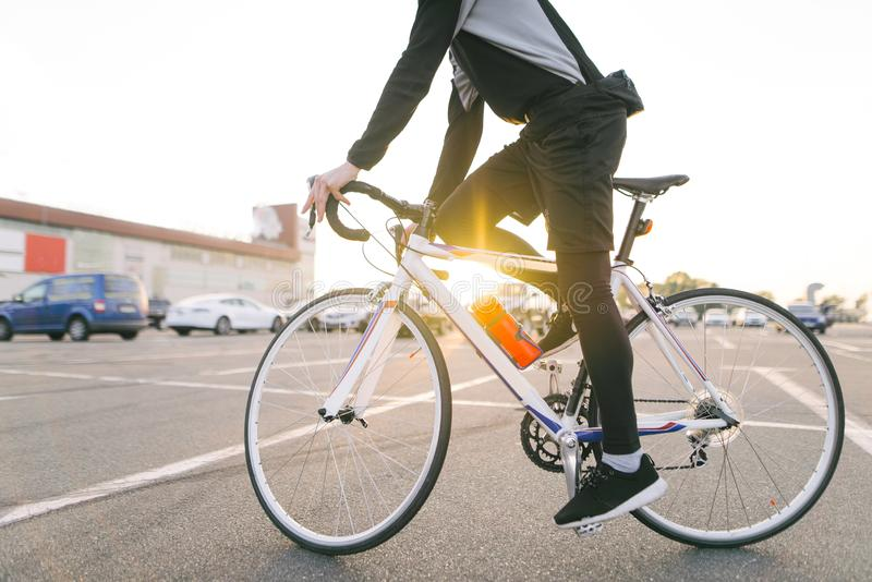 Junger Reiter im dunklen Fahrrad trägt ein Fahrrad auf einem Straßenhintergrund und -sonnenschein im Sonnenuntergang stockfotos