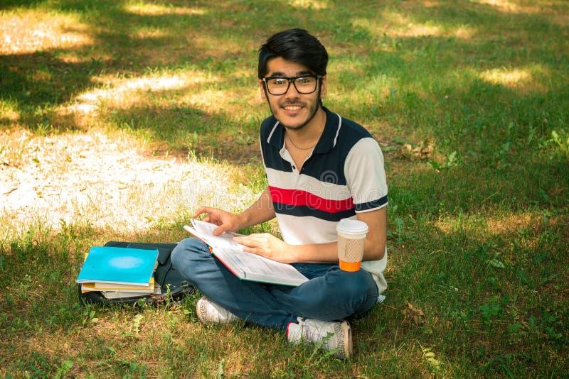Junger reizend netter Kerl sitzt auf dem Gras, welches die Kamera betrachtet stockbild