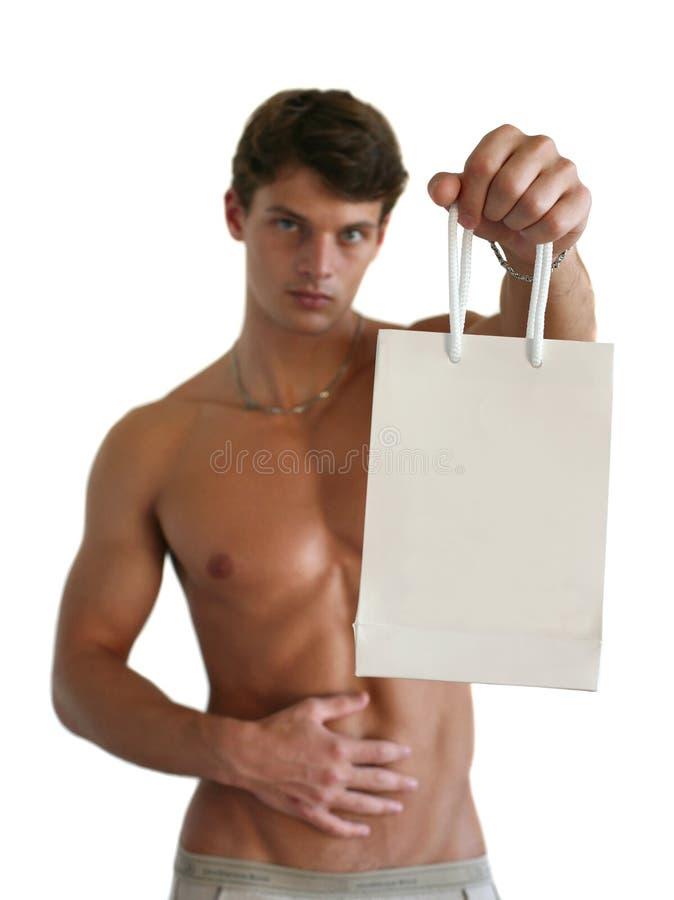 Junger reizvoller Mann mit einer Einkaufstasche lizenzfreie stockfotografie